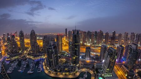 Aerial top view of Dubai Marina night to day transition timelapse. Promenade and canal with floating yachts and boats before sunrise in Dubai, UAE. Illuminated modern towers and traffic on the road