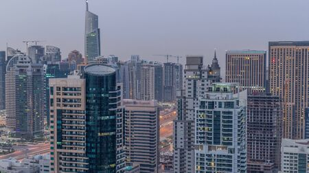 Aerial top view of Dubai Marina and JLT night to day transition timelapse. Skyscrapers before sunrise in Dubai, UAE. Illuminated modern towers and traffic on the road Stock fotó