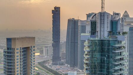 Aerial top view of sunrise in Dubai Marina and JLT timelapse. Skyscrapers at morning in Dubai, UAE. Modern towers and traffic on the road