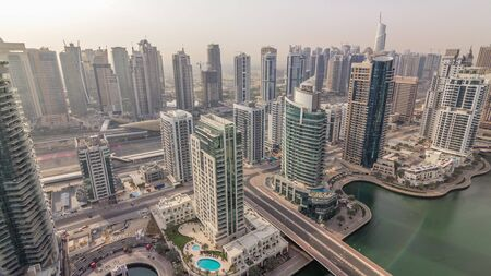 Aerial top view of Dubai Marina and JLT morning timelapse. Promenade and canal with floating yachts and boats after sunrise in Dubai, UAE. Modern towers and traffic on the road