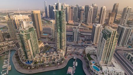 Aerial top view of Dubai Marina and JLT evening timelapse. Promenade and canal with floating yachts and boats before sunset in Dubai, UAE. Modern towers and traffic on the road Stock fotó