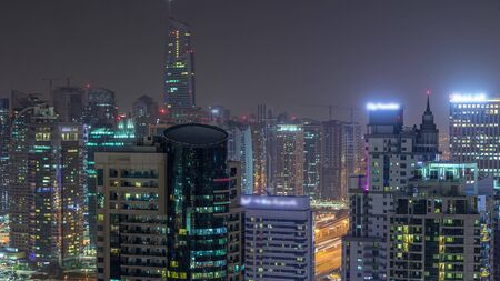Aerial top view of Dubai Marina and JLT night timelapse. Skyscrapers from above in Dubai, UAE. Illuminated modern towers and traffic on the road