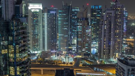 Aerial top view of Dubai Marina and JLT night timelapse. Skyscrapers from above in Dubai, UAE. Illuminated modern towers and traffic on the road Stock fotó