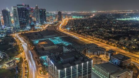 Jumeirah Lake Towers residential district aerial night timelapse near Dubai Marina. Illuminated modern skyscrapers and traffic from above. Villas and houses on a background Stock fotó