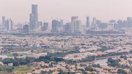 Aerial view of apartment houses and villas in Dubai city timelapse near jumeirah lake towers district, United Arab Emirates. Towers and construction site on a background. Top fiew from skyscraper Stock fotó