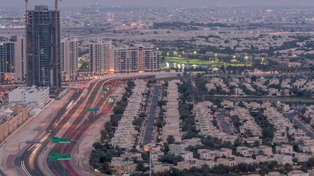 Jumeirah Lake Towers residential district aerial day to night transition timelapse near Dubai Marina. Illuminated modern skyscrapers and traffic on the road from above