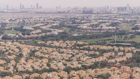 Aerial view of apartment houses and villas with golf course in Dubai city timelapse near jumeirah lake towers district, United Arab Emirates. Top fiew from skyscraper Stock fotó