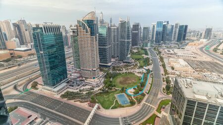 Jumeirah Lake Towers residential district aerial timelapse near Dubai Marina. Modern skyscrapers and park from above