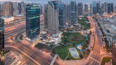 Jumeirah Lake Towers residential district aerial day to night transition timelapse near Dubai Marina. Illuminated modern skyscrapers and park from above