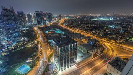 Jumeirah Lake Towers residential district aerial night timelapse near Dubai Marina. Illuminated modern skyscrapers and traffic from above. Villas and houses on a background