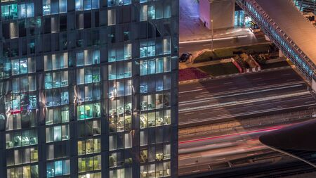 Night view of office and apartment building timelapse in Dubai downtown. High rise skyscraper with blinking windows and traffic. Aerial view from above. 스톡 콘텐츠