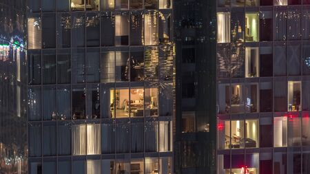 Night view of office and apartment building timelapse. High rise skyscraper with blinking windows with people moving inside. Aerial view from above. Zoom out
