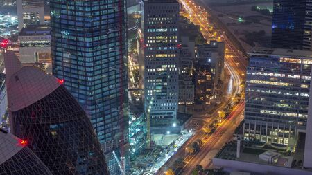 Skyline of the buildings near Sheikh Zayed Road and DIFC aerial night timelapse in Dubai, UAE. Modern towers and illuminated skyscrapers in financial center and downtown Archivio Fotografico