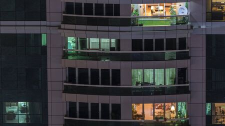 Night view of exterior apartment building timelapse. High rise skyscraper with blinking lights in windows with people moving inside. Pan right 스톡 콘텐츠