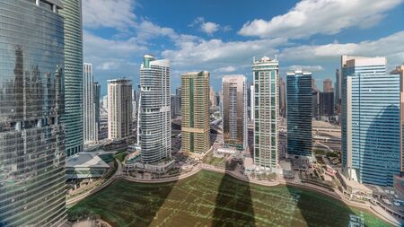 Residential apartments and offices in Jumeirah lake towers district timelapse in Dubai. Aerial panoramic view from above with modern skyscrapers and clouds on blue sky