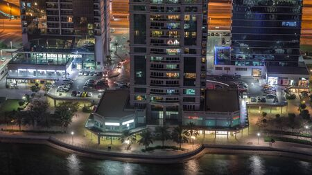 Residential and office buildings in Jumeirah lake towers district night timelapse with shops, restaurants and walkways in Dubai. Aerial panoramic view from above with modern skyscrapers Stock fotó