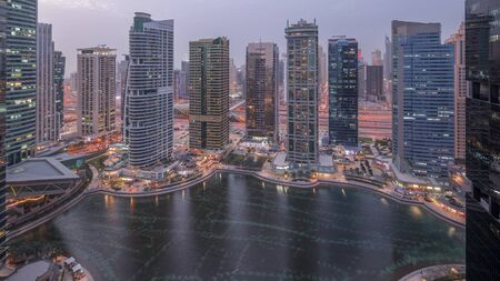 Residential and office buildings in Jumeirah lake towers district day to night transition timelapse in Dubai. Aerial panoramic view from above with modern skyscrapers