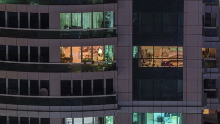 Night view of exterior apartment building timelapse. High rise skyscraper with blinking lights in windows with people moving inside