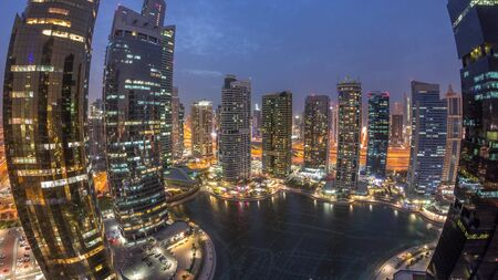 Residential and office buildings in Jumeirah lake towers district day to night transition timelapse in Dubai. Aerial panoramic view from above with modern skyscrapers Stock fotó