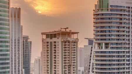 Sunset over residential and office buildings in Jumeirah lake towers district timelapse in Dubai. Aerial panoramic view from above with modern skyscrapers Stock fotó