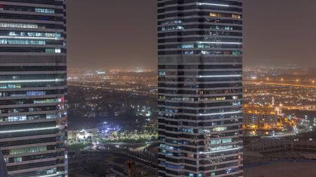 Office buildings in Jumeirah lake towers district night timelapse with blinking lights in windows in Dubai. Aerial view from above with modern skyscrapers