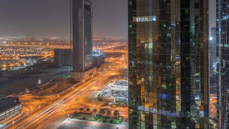 Office buildings in Jumeirah lake towers district night timelapse in Dubai. Aerial panoramic view from above with modern skyscrapers, traffic on a road and parking