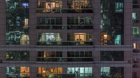 Night view of exterior apartment building timelapse. High rise skyscraper with blinking lights in windows with people moving inside. Zoom in