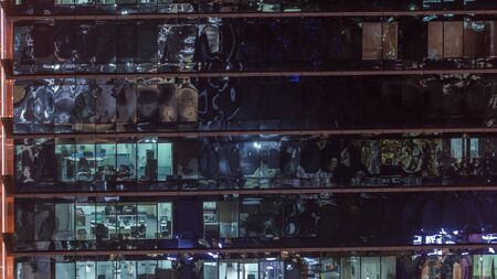 Office skyscraper exterior during late evening with interior lights on and people working inside night timelapse. Aerial close up view from above with many windows. Zoom in Stock fotó
