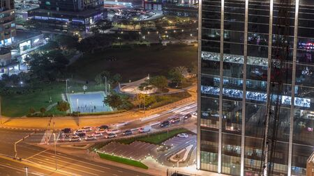 Residential and office buildings in Jumeirah lake towers district night timelapse with park and traffic on intersection in Dubai. Aerial panoramic view from above with modern skyscrapers Stock fotó