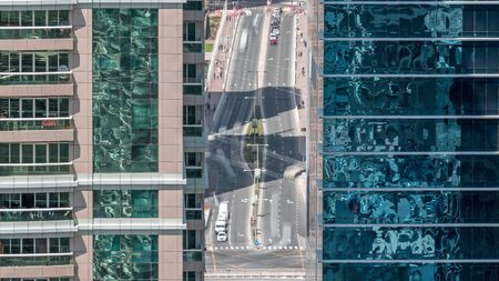 Residential and office buildings in Jumeirah lake towers district morning timelapse with in Dubai. Aerial panoramic view from above with traffic on a road between modern skyscrapers