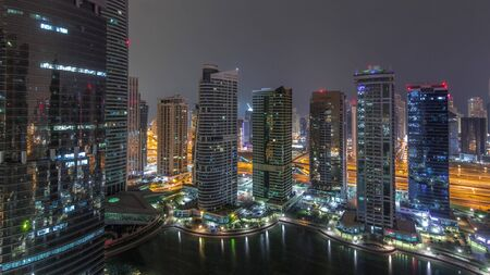 Residential and office buildings in Jumeirah lake towers district during all night timelapse with lights switching off in Dubai. Aerial panoramic view from above with modern skyscrapers Stock fotó