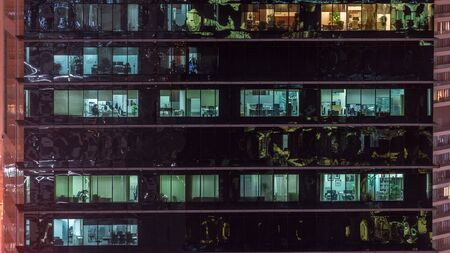 Office skyscraper exterior during late evening with interior lights on and people working inside night timelapse. Aerial close up view from above with many windows. Pan up