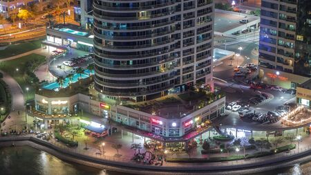 Residential and office buildings in Jumeirah lake towers district night timelapse with shops, restaurants and walkways in Dubai. Aerial panoramic view from above with modern skyscrapers