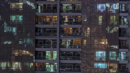 Night view of exterior apartment building timelapse. High rise skyscraper with blinking lights in windows with people moving inside. Pan up
