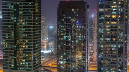 Residential and office buildings in Jumeirah lake towers district night timelapse with blinking lights in windows in Dubai. Aerial view from above with modern skyscrapers Banco de Imagens