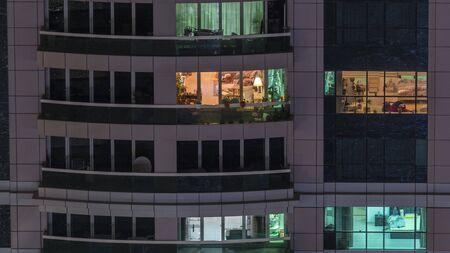 Night view of exterior apartment building timelapse. High rise skyscraper with blinking lights in windows with people moving inside. Pan right