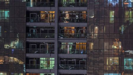Night view of exterior apartment building timelapse. High rise skyscraper with blinking lights in windows with people moving inside. Zoom in Stock Photo