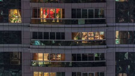 Night view of exterior apartment building timelapse. High rise skyscraper with blinking lights in windows with people moving inside. Pan down