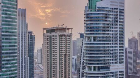 Sunset over residential and office buildings in Jumeirah lake towers district timelapse in Dubai. Aerial panoramic view from above with modern skyscrapers
