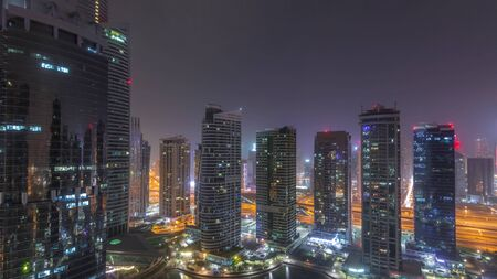 Residential and office buildings in Jumeirah lake towers district during all night timelapse with lights switching off in Dubai. Aerial panoramic view from above with modern skyscrapers