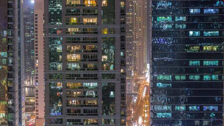 Residential and office buildings in Jumeirah lake towers district night timelapse with blinking lights in windows in Dubai. Aerial view from above with modern skyscrapers