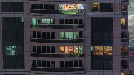 Night view of exterior apartment building timelapse. High rise skyscraper with blinking lights in windows with people moving inside. Pan down Stock Photo