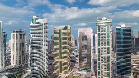 Residential apartments and offices in Jumeirah lake towers district timelapse in Dubai. Aerial panoramic view from above with modern skyscrapers and clouds on blue sky Stock fotó