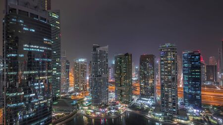 Residential and office buildings in Jumeirah lake towers district night timelapse in Dubai. Aerial panoramic view from above with modern skyscrapers Stock fotó