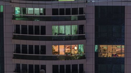 Night view of exterior apartment building timelapse. High rise skyscraper with blinking lights in windows with people moving inside. Zoom out