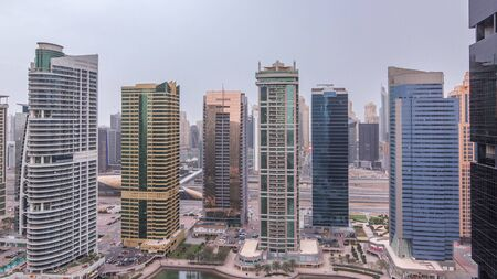 Residential and office buildings in Jumeirah lake towers district night to day transition timelapse before sunrise in Dubai. Aerial panoramic view from above with illuminated modern skyscrapers Stock fotó