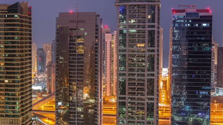 Residential and office buildings in Jumeirah lake towers district night to day transition timelapse before sunrise in Dubai. Aerial panoramic view from above with illuminated modern skyscrapers