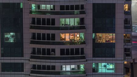 Night view of exterior apartment building timelapse. High rise skyscraper with blinking lights in windows with people moving inside. Zoom in 스톡 콘텐츠