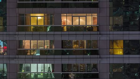 Night view of exterior apartment building timelapse. High rise skyscraper with blinking lights in windows with people moving inside. Pan right Stock fotó