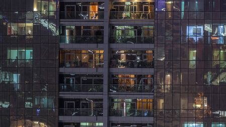 Night view of exterior apartment building timelapse. High rise skyscraper with blinking lights in windows with people moving inside. Pan down 스톡 콘텐츠